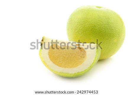 green sweet grapefruit and a cut piece on a white background - stock photo