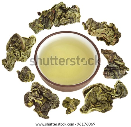 Green tea balls oolong in clay teacup  isolated on white - stock photo