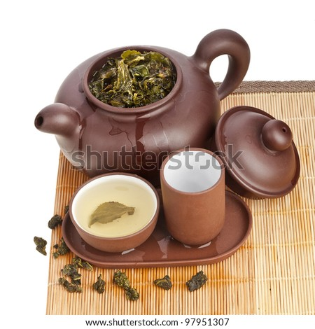 Green tea balls oolong in clay teapot and teacup isolated on white - stock photo
