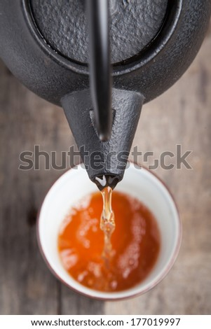 Green tea being poured out of a Japanese teapot - stock photo