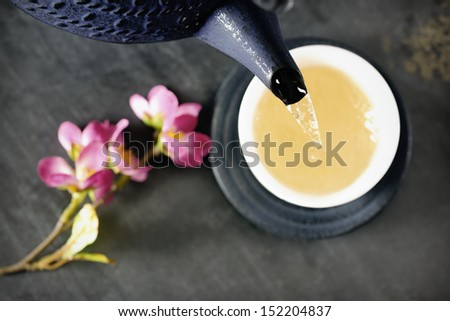 Green tea being poured out of a Japanese teapot, pink cherry blossom twig in the background, selective focus - stock photo