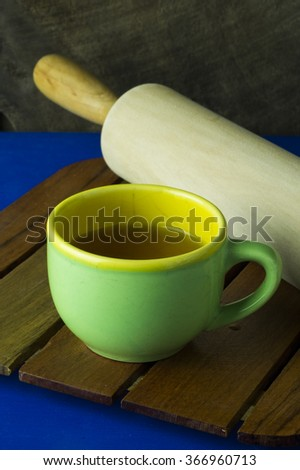 Green tea cup with wooden rolling pin - stock photo