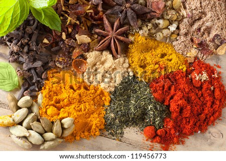 Green tea, herbs and spices on a wooden table - stock photo