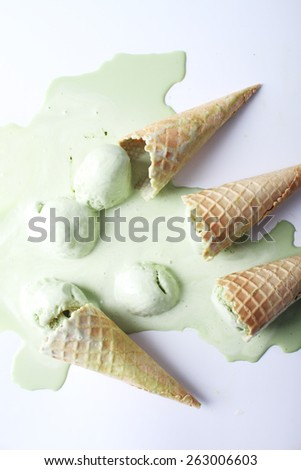 green tea ice cream cones dropped on white background - stock photo