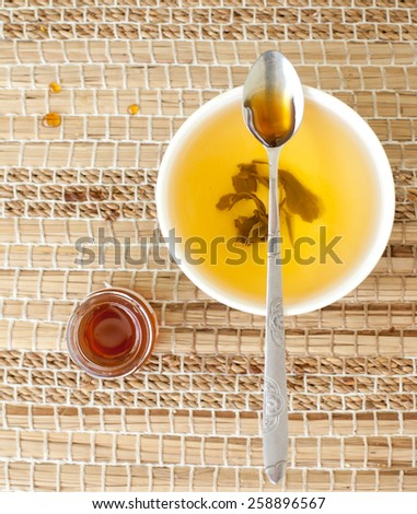 Green tea in a ceramic bowl  with  honey on a wooden background. Selective focus - stock photo