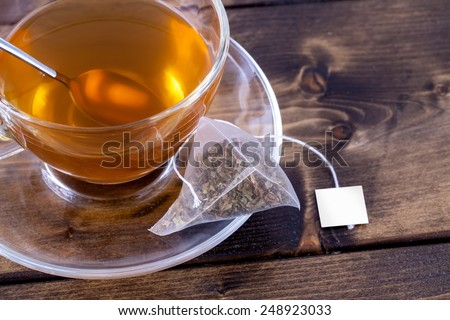 Green tea in a glass teacup on a rustic wooden table - stock photo
