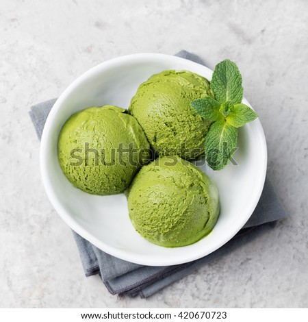 Green tea matcha ice cream scoop in white bowl on a grey stone background Copy space Top view - stock photo