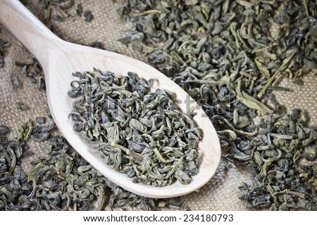Green tea on wooden spoon in studio.  - stock photo