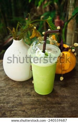 Green tea smoothies on wooden table - stock photo