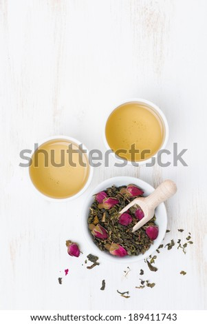 green tea with rosebuds and cups on a white table, top view, vertical - stock photo