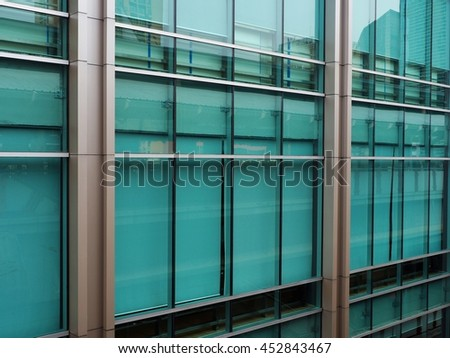 Green tempered safety glass on modern glass building - stock photo