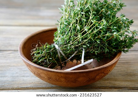 Green thyme in a bowl on boards, close up - stock photo