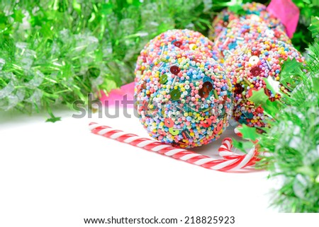 Green tinsel with Christmas balls and candy canes - stock photo