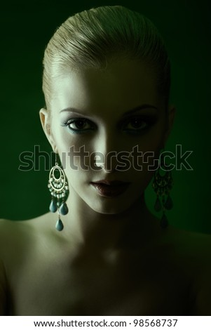 green tinted portrait of beautiful young blonde woman in jewellery - stock photo