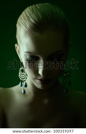 green tinted portrait of beautiful young blonde woman in jewellery with eyes closed - stock photo