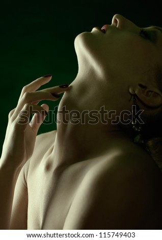 green tinted portrait of beautiful young blonde woman in jewelry touching her neck with manicured fingers - stock photo