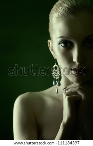 green tinted portrait of beautiful young blonde woman in jewelry with hands below her chin - stock photo