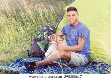 Green tourism.  Portrait of a young handsome tourist wearing blue t-short and beige shorts, sitting on a plaid holding a map looking at the camera smiling, green tent on the background - stock photo