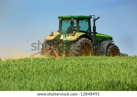 Green tractor working in the field. - stock photo