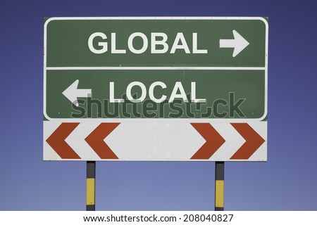 green traffic sign in front of a blue sky, horizontal arrows showing two directions and a red white road warning post. Business concept for the relations or conflicts between Europe and Africa - stock photo