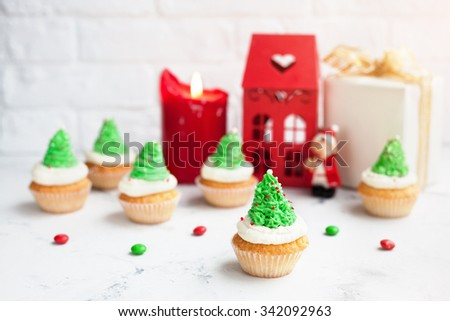 Green tree cupcakes near red house, candle and present at Christmas time - stock photo