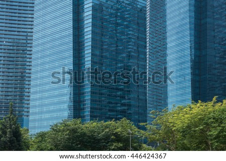 Green tree standing in front of the commercial buildings - stock photo