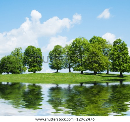 green trees and cloudy sky on lake - stock photo