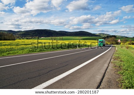 Green truck arrives from a distance on an asphalt road between the yellow flowering rapeseed field in the rural landscape. Wooded mountains in the background. Blue sky with white clouds. - stock photo