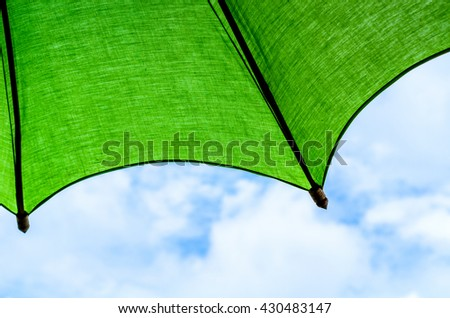 green umbrella in a clear blue sky,colorful sunshades umbrellas on blue sky - stock photo