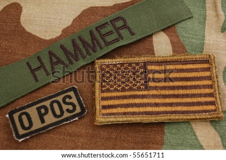 Green US flag, name tag and blood type patch on woodland camo background - stock photo