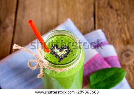 Green vegetable and herbs smoothie with heart of poppy and sesame seeds. Love for a healthy raw food concept. - stock photo