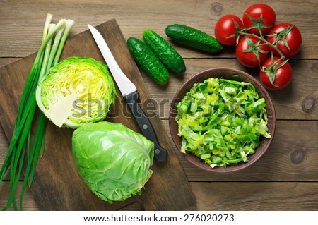 Green vegetable salad of cabbage, cucumbers and spring onion in bowl and vegetables on brown wooden table. Top view point. - stock photo