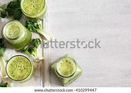 Green vegetable smoothie in jars and ingredients on the white wooden background. Diet concept with text space. Detox. Vegetarian food - stock photo