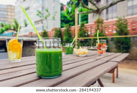 Green vegetable smoothies and infused fruit water cocktails over a wooden table outdoors. Healthy organic summer drinks concept. - stock photo