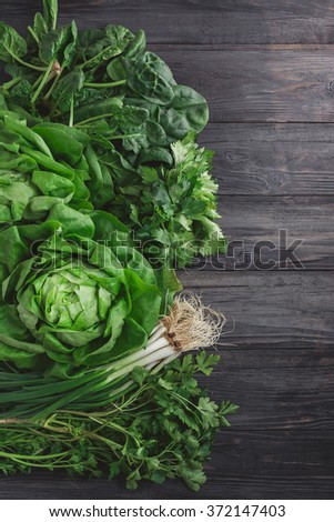 Green vegetables on wooden background (spring onions, parsley, lettuce and spinach) - stock photo