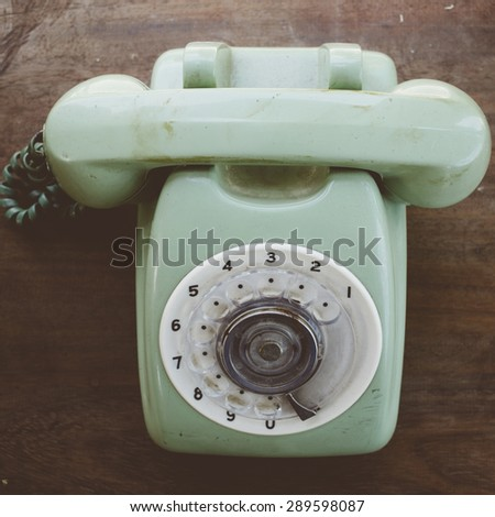 Green vintage telephone on brown wood desk background - stock photo