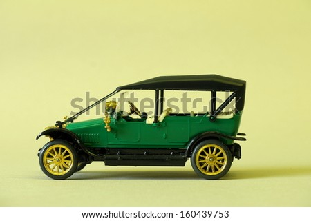 green vintage toy car on a yellow background - stock photo