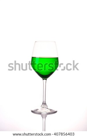 Green water in wine glass on white background  - stock photo