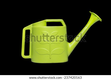 Green watering pot on black background. - stock photo
