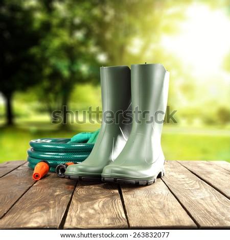 green wellies and a garden hose - stock photo