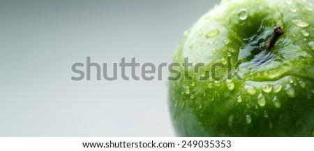 green wet apple with big water droplet, macro shot - stock photo
