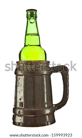 green wet bottle of beer is inserted in a brown ceramic mug - stock photo