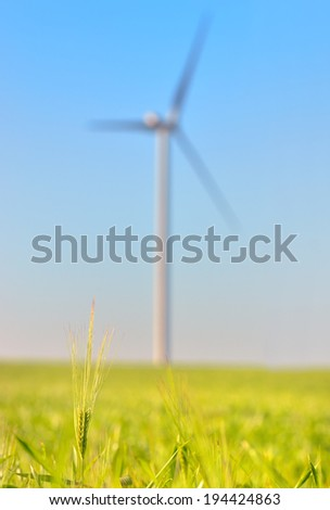 Green wheat field with blue sky and wind power Energy Generator in the background - stock photo