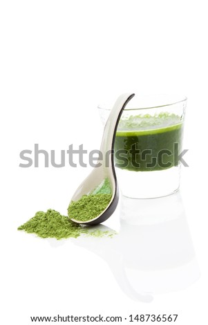 Green wheatgrass, spirulina and chlorella juice in glass isolated on white background with wheat grass powder on ceramic spoon.  - stock photo