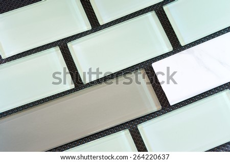 green white and taupe colored glass and porcelain subway tile or backsplash against black background arranged in rows  - stock photo
