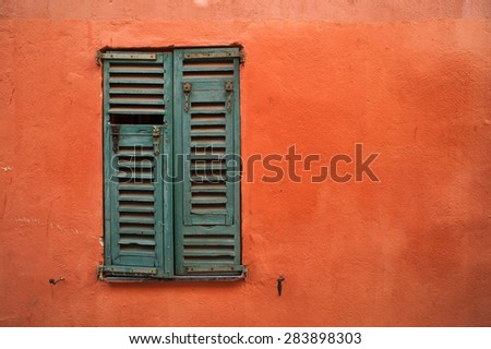 green window shutters on orange texture wall - stock photo