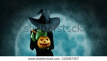 Green witch opening Halloween carved pumpkin on full moon background. Halloween, horror theme - stock photo