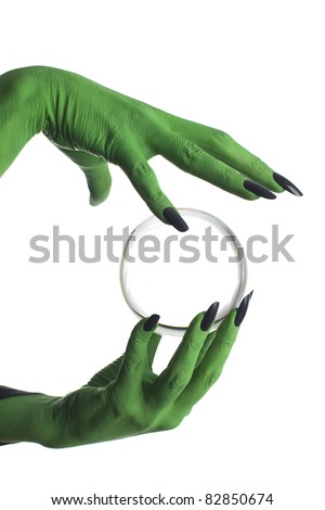 Green witch's hand holding crystal ball, white background. - stock photo
