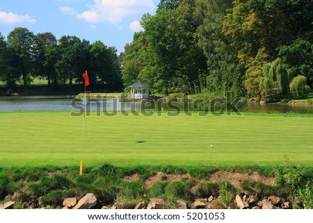 Green with golf hole on an island - stock photo
