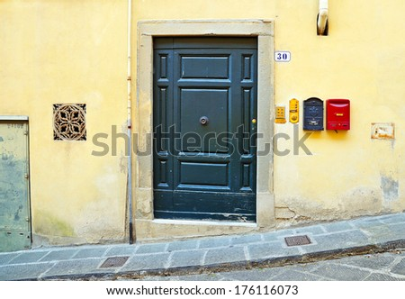 Green wooden door and mailboxes on a yellow wall in Italy. - stock photo